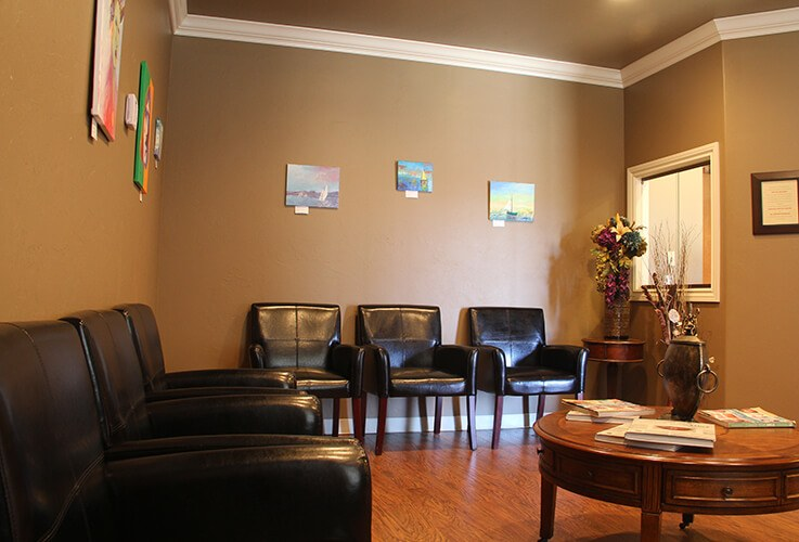 waiting room with brown leather chairs and wood floors