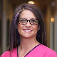 Young lady wearing glasses and pink scrubs