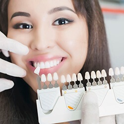 Woman smiling holding a dental tooth shade chart