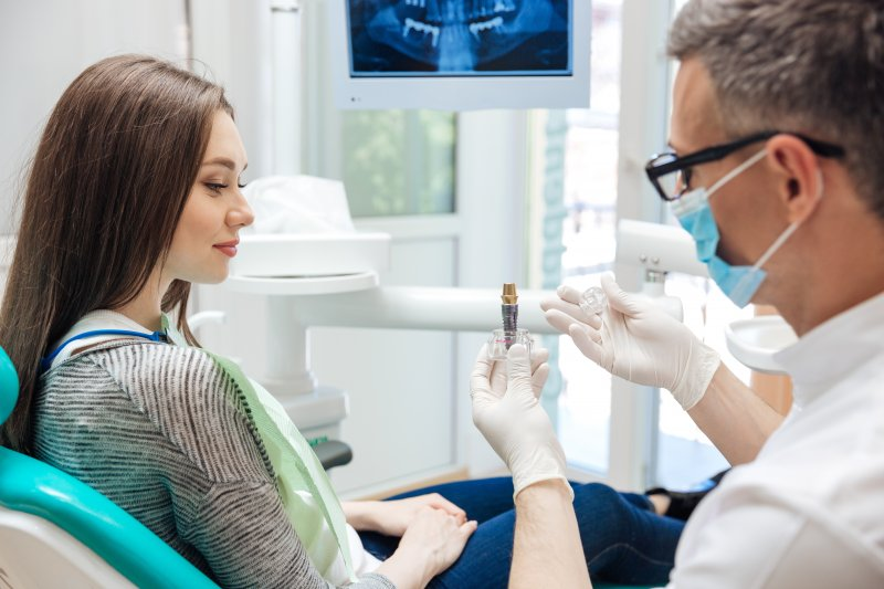 Male dentist showing female patient a dental implant