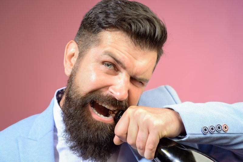 Man opening Champagne bottle with teeth