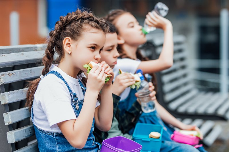 Three children eating their school lunches